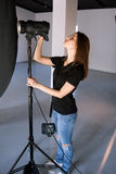 El fotógrafo de la muchacha ajusta la luz en estudio fotos de archivo