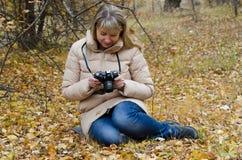 El fotógrafo de la muchacha mira a través de la cantidad del otoño Foto de archivo