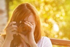El fotógrafo de la muchacha toma imágenes contra la perspectiva del verdor Front View Imagen de archivo