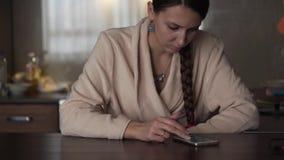El fotógrafo de la muchacha toma imágenes de texturas y de la naturaleza Señora atractiva en albornoz beige con smartphone en la  almacen de metraje de vídeo