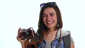 El fotógrafo de la mujer bastante joven con la cámara vieja del vintage que tomaba la imagen, estudio tiró en el fondo blanco Her metrajes