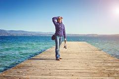 El fotógrafo de la mujer joven emite el lago di Garda Italia de Sirmione del embarcadero del puente del sol de la mañana Fotos de archivo libres de regalías