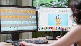 El fotógrafo de sexo femenino profesional utiliza un favorable software que corrige almacen de metraje de vídeo