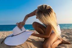 El fotógrafo en el trabajo, muchacha adorna el sombrero en la playa Foto de archivo