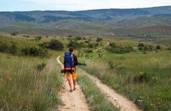 El fotógrafo está caminando abajo del camino a la montaña Imagenes de archivo