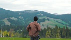 El fotógrafo inspirado aumenta sus manos para arriba en montañas metrajes