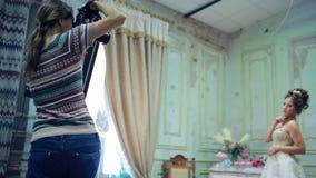 El fotógrafo joven está tomando a imágenes la novia almacen de video