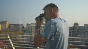 El fotógrafo mira la cámara, contra el contexto de la ciudad almacen de metraje de vídeo