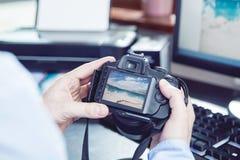 El fotógrafo mira las imágenes Imagen de archivo libre de regalías