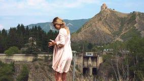 El fotógrafo profesional, mujer rubia joven en vestido rosa claro del vuelo del verano, señora toma imágenes de georgiano almacen de metraje de vídeo