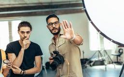 El fotógrafo que ajusta la actitud del modelo durante una foto shoo fotos de archivo
