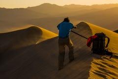 El fotógrafo que es soplado por el viento está enmarcando su tiro en el parque nacional de Death Valley Foto de archivo