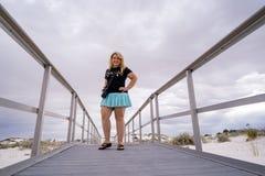 El fotógrafo rubio adorable de la mujer se coloca en los paseos marítimos de las arenas blancas nanómetro foto de archivo