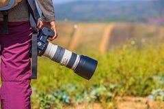 El fotógrafo sostiene su cámara de DSLR imagen de archivo libre de regalías