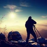 El fotógrafo toma la imagen de las rocas del helada cubiertas con nieve fresca del polvo Foto de archivo libre de regalías