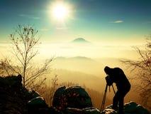 El fotógrafo toma la imagen de las rocas del helada cubiertas con nieve fresca del polvo Imágenes de archivo libres de regalías