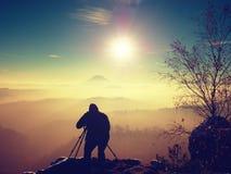 El fotógrafo toma la imagen de las rocas del helada cubiertas con nieve fresca del polvo Imagenes de archivo