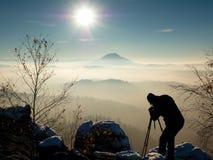 El fotógrafo toma la imagen de las rocas del helada cubiertas con nieve fresca del polvo Imagen de archivo