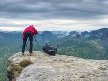 El fotógrafo toma las fotos con la cámara en el trípode en pico de montaña rocosa Fotos de archivo