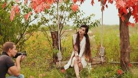 El fotógrafo toma las fotos de la muchacha de Vietnam del asiático en el jardín del otoño almacen de video