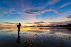 El fotógrafo toma una foto en puesta del sol colorida Fotos de archivo libres de regalías