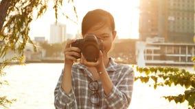 El fotógrafo vietnamita de la muchacha toma imágenes de la naturaleza en el centro de ciudad en la puesta del sol Foto de archivo libre de regalías