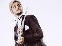 El frac que lleva del flautista de sexo masculino sostiene la flauta Imagen de archivo libre de regalías