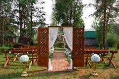 El fragmento le gusta la vista de sillas agradables y del arco listos para la ceremonia de boda Imagen de archivo libre de regalías