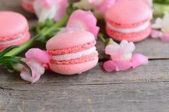 El francés popular apelmaza macarons Macarons y flores rosas claros en un fondo de madera del vintage con el espacio de la copia  Imagen de archivo libre de regalías