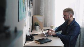El freelancer casero de sexo masculino joven con los vidrios y el pelo amarillo se abre y comienza usando el ordenador portátil L metrajes