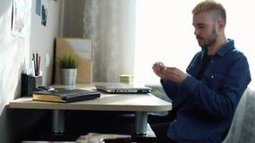 El freelancer casero de sexo masculino joven con los vidrios y el pelo amarillo toma los vidrios abre y comienza a usar el ordena almacen de metraje de vídeo