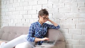 El freelancer de la muchacha viste los vidrios y comienza a trabajar en un ordenador portátil en casa La visten en los vaqueros b almacen de metraje de vídeo