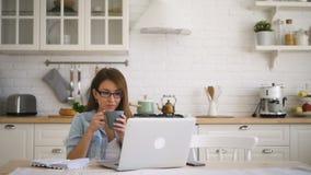 El freelancer de la mujer está trabajando con el ordenador portátil, café de consumición, sentando en casa la cocina almacen de video
