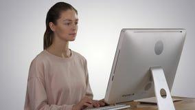 El freelancer de la mujer está trabajando en un nuevo proyecto sobre el ordenador en fondo de la pendiente almacen de metraje de vídeo
