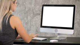 El freelancer de la mujer está trabajando en un nuevo proyecto sobre el ordenador Visualización blanca almacen de video
