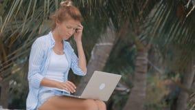 El freelancer de la mujer trabaja en la playa almacen de video