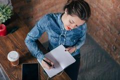 El freelancer de sexo femenino joven hermoso con la libreta y la tableta tienen un descanso para tomar café foto de archivo