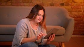 El freelancer de sexo femenino de pelo largo gordo se sienta en el piso que trabaja con la tableta atento en atmósfera casera aco almacen de metraje de vídeo
