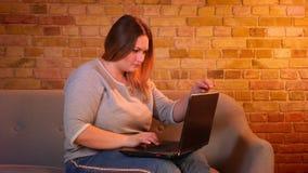 El freelancer de sexo femenino de pelo largo gordo se sienta en el sofá que mecanografía atento en el ordenador portátil en atmós almacen de metraje de vídeo