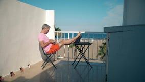 El freelancer de sexo masculino hermoso trabaja en su ordenador portátil mientras que se sienta en terraza del seaview metrajes