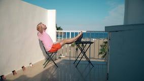 El freelancer feliz acaba sus trabajos sobre el ordenador portátil mientras que se sienta en terraza del seaview almacen de metraje de vídeo