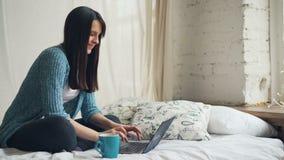 El freelancer feliz de la mujer hermosa está trabajando en casa usando el ordenador portátil y está sonriendo mirando la pantalla metrajes