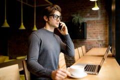 El freelancer hermoso en vidrios del ojo habla smartphone mientras que en el ordenador portátil Imagen de archivo libre de regalías