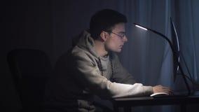 El freelancer joven agotado despierta delante del ordenador en la noche metrajes
