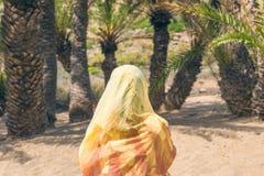 El freelancer musulmán de la mujer en una bufanda colorida se sienta en la playa dubai Viaje Halal foto de archivo libre de regalías