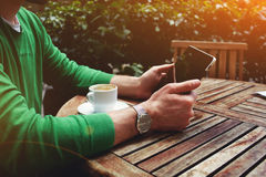 El Freelancer que se sienta en la terraza con la taza de café y la pantalla táctil hacen tabletas mientras que teniendo una rotur fotografía de archivo