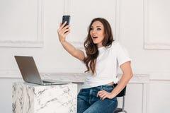 El freelancer sorprendido de la muchacha con un ordenador portátil y un teléfono en su mano hace el selfie Mujer joven con una ca fotos de archivo libres de regalías