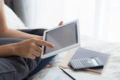 El Freelancer trabaja en casa, usando la tableta, apps del calendario imagenes de archivo