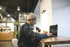 El freelancer trabaja para un ordenador portátil en un café acogedor Un estudiante que se sienta en un café en la tabla y que usa Foto de archivo libre de regalías