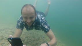 El Freelancer utiliza un smartphone mientras que se zambulle bajo el agua en la cámara lenta Lago natural almacen de metraje de vídeo